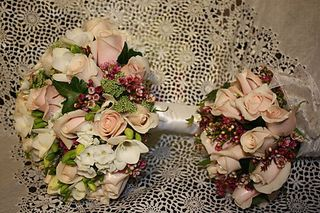Candy Bianca roses, white phlox, white freesia, ivy, queen annes lace, and wax flower.