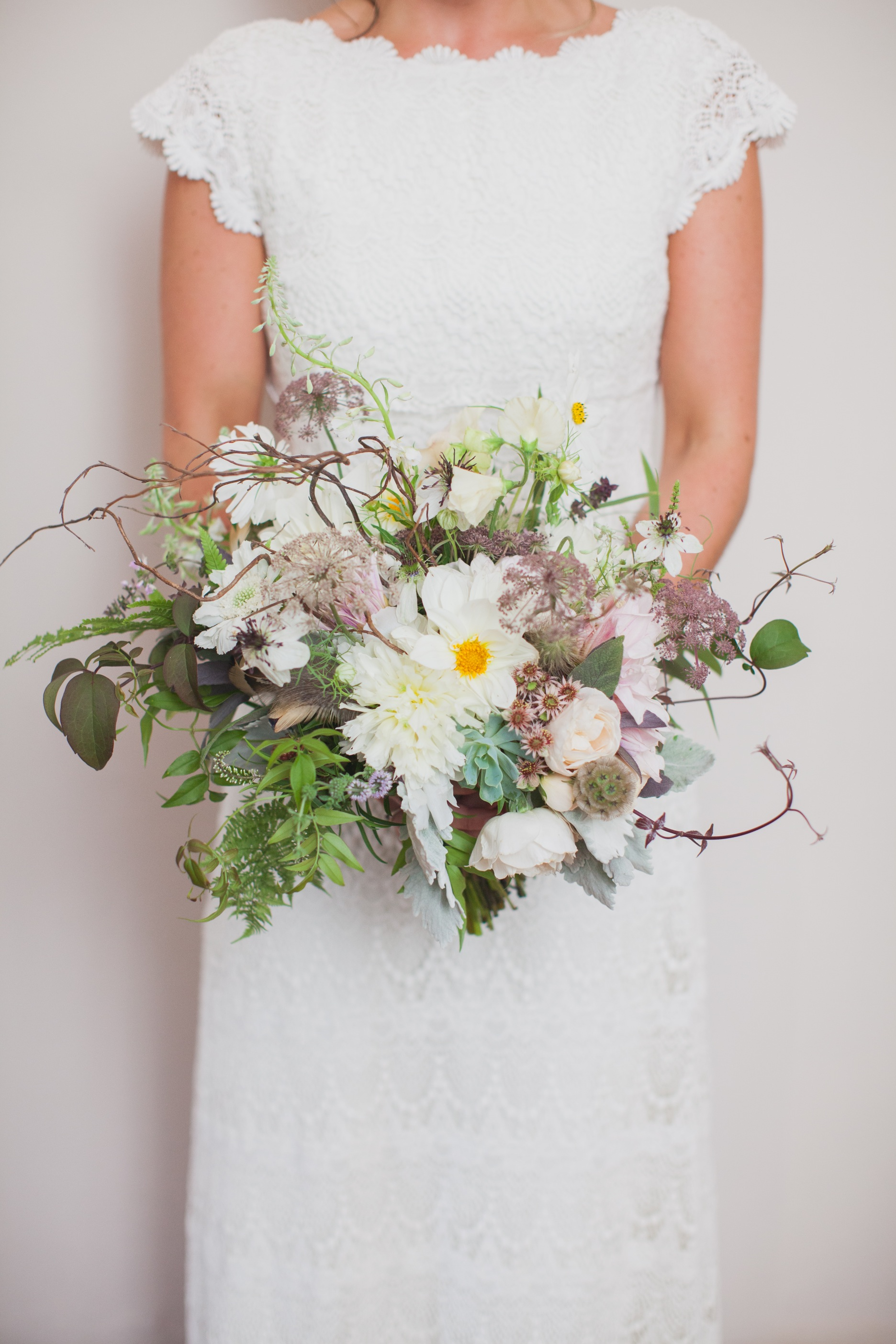 Bridal bouquet by designer Susan Hatwood of The Blue Carrot - Portscatho, Cornwall, United Kingdom, with white peonies, dahlias, sweet pea, scabiosa, larkspur, Queen Anne's lace, astrantia, succulents, dusty miller, jasmine vine, fern, curly willow and feathers