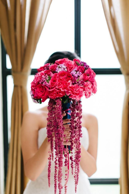 Cascading bridal bouquet by designer Maria Limon of Maria Limon Atelier - Mexico City, Mexico, with fuchsia roses, carnations and red hanging amaranthus