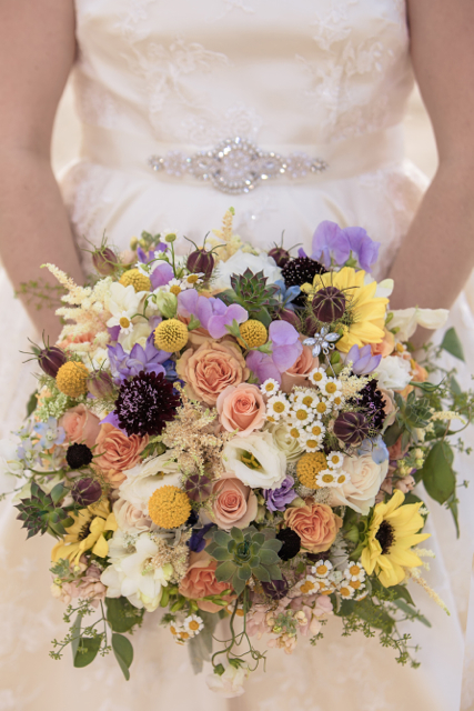 Bridal Bouquet by designer Daevid Reed of Daevids Flowers and Decor - Norfolk, Virginia, with peach roses, astilbe, craspedia, lavender sweet pea, lisianthus, chamomile, love in the mist, succulents and seeded eucalyptus