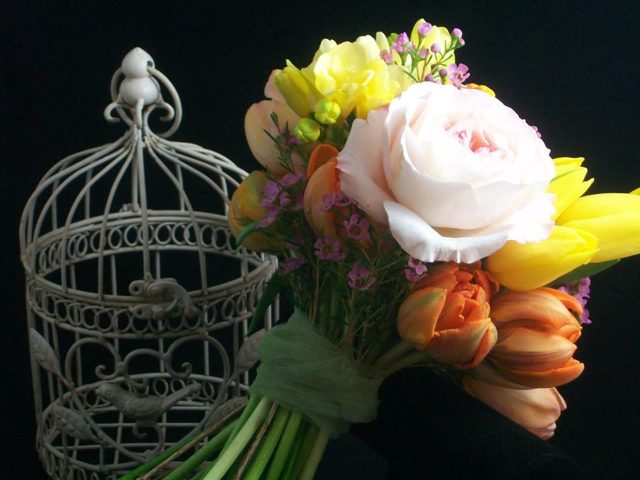 Wedding bouquet by designer Amy Santee from Amy's Wedding and Event Flowers - Aurora, Colorado, with garden roses, orange tulips, yellow tulips, freesia and wax flower