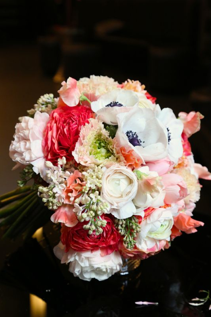 Bridal bouquet by designer Jennifer Ederer of Modern Day Floral - Grand Rapids, MI, with coral ranunculus, coral sweet pea, blush ranunculus, white lilacs, white ranunculus and black and white anemones