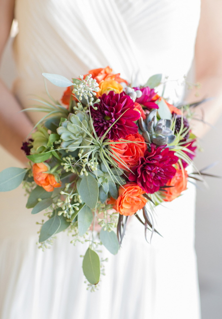 Bridal bouquet by Designer Susan Kelly of Three Sisters Custom Flowers and Events – California, with burgundy dahlias, orange roses, orange ranunculus, green hellebores, succulents, tillandsias, agonis an seeded eucalyptus