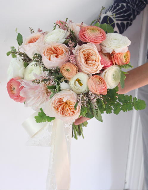 Bridal bouquet by designer Holly Rutt of Sweet Pea Floral – Michigan, with Juliet garden roses, coral ranunculus, café au lait dahlias, white ranunculus, calcynia, maidenhair fern and cascading ribbon