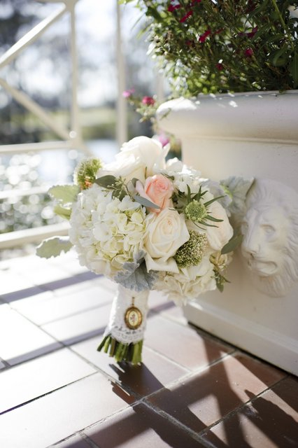 Bridal bouquet by designer Madeleine Elmer of Fleur de Vie – Houston, Texas, with white hydrangea, blush roses, white roses, white trachelium, white scabiosa, dusty miller and seeded eucalyptus