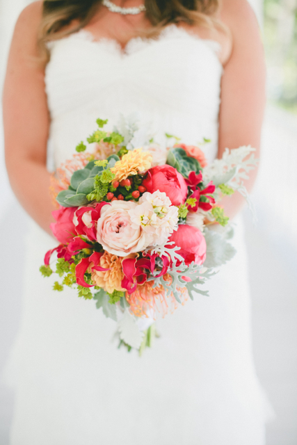 Bridal bouquet by Designer Nicole Boshard of The Petal Pusher – California, with coral charm peonies, gloriosa lilies, peach dahlias, pin cushion protea, hypericum, stock, garden roses, succulents, bupleurum and dusty miller