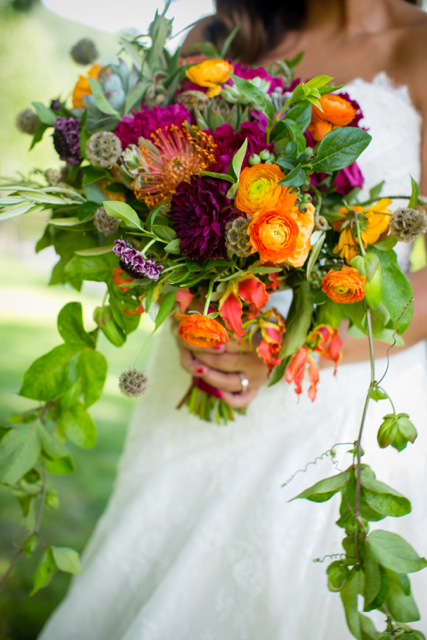 Cascading bridal bouquet by designer Jeanette Kleitz of True Florette - Orangeburg, New York, with orange pincushion protea, orange ranunculus, gloriosa lilies, plum dahlias, scabiosa, scabiosa pods, succulents and passion flower vine