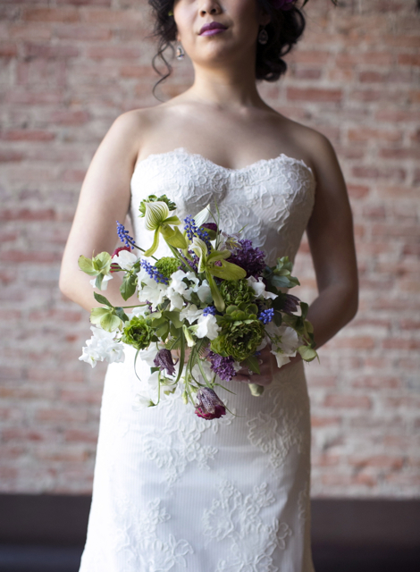 Bridal bouquet by designer Susan McLeary owner of Passionflower - Ann Arbor, Michigan, with lady slipper orchids, green ranunuculus, green hellebores, grape hyacinth, white sweet pea, purple parrot tulips, lilacs and fritillaria