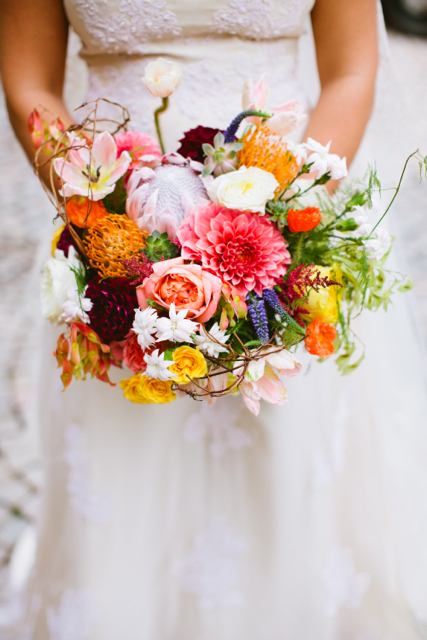 Bridal bouquet by designer Amy Dunlap of Amy Lynn Originals - Winston-Salem, NC, with orange pincushion protea, coral and burgundy dahlias, king protea, blush tulips, yellow spray roses, coral garden roses, succulents, astilbe, veronica and tree of heaven