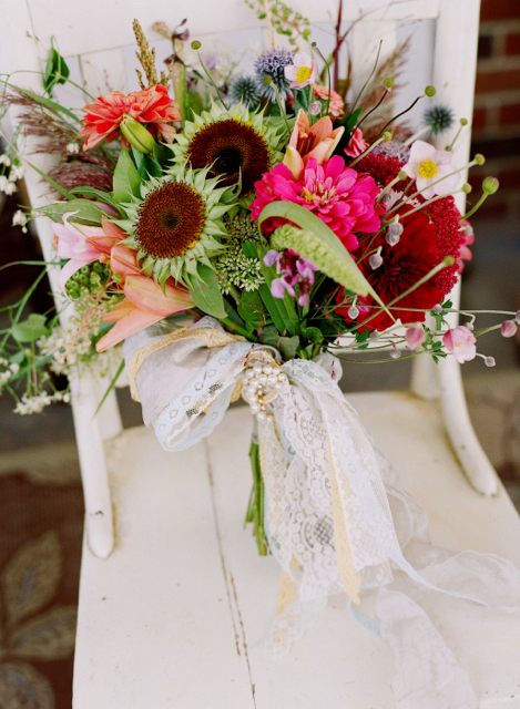 Bridal bouquet by designers Mary Coombs and Dawn Clark from A Garden Party - Elmer, New Jersey, with sun flower centers, pink zinnia, burgundy dahlias, blush Japanese anemones, coral lilies, globe thistle, poke weed, millet and vintage ribbons