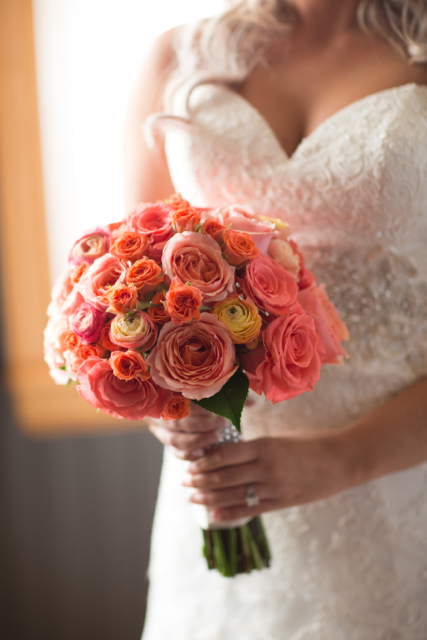 Bridal bouquet by Designers Carol and Peggy of Celebration Florals - Corvallis, Oregon, with coral and orange roses and ranunculus
