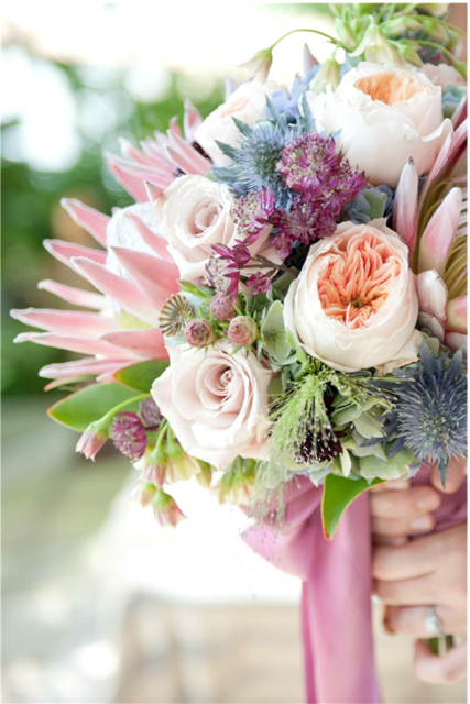 Bridal bouquet by designer Isha Foss of Isha Foss Events - Virginia Beach, Virginia, with king protea, Juliet garden roses, poppy pods, Quicksand roses, leucadendron, burgundy astrantia, green hydrangea, thistle and allium