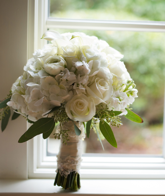 Wedding bouquet by designer Melissa Stewart of Primrose Floral and Event Design - Lexington, Massachusetts, with white hydrangea, roses, ranunculus, stock, mini callas and seeded eucalyptus
