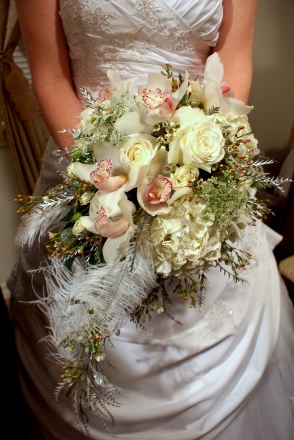 Cascading bridal bouquet by designer Julia Miller of Julia's Floral - Edgewood, Washington, with white hydrangea, white roses, white cymbidium orchids, Queen Anne's lace, wax flower, grevillea and ostrich feathers