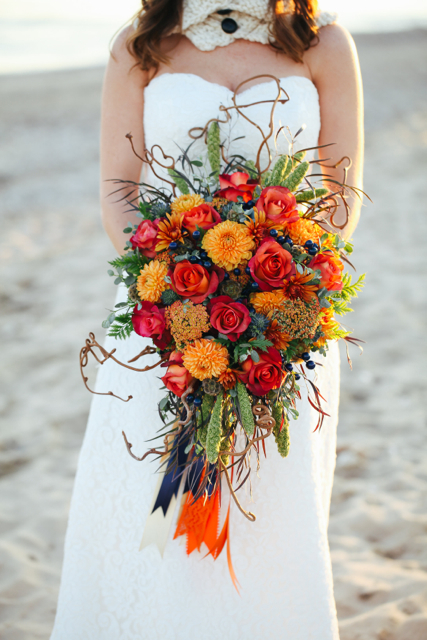 Cascading bridal bouquet by designer Alicia Jayne Florals - Southern Maryland, with orange dahlias, rust roses, yarrow, blue berries, thistle, green millet, scabiosa pods, agonis, gunnii eucalyptus, kiwi vine and cascading ribbons
