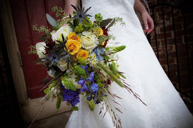 Cascading bridal bouquet by Designers Peggy and Hunter Sherwood of Sherwood Events - Lexington, Kentucky, with blue hydrangea, delphinium, thistle, star of Bethlehem, white roses, yellow spray roses, bupleurum, seeded eucalyptus, chamomile and native grasses