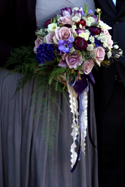 Wedding bouquet by designer Laurie Garza of Fleurie - Reedley, California, with amnesia roses, purple hydrangea, purple kale, purple freesia, wine ranunculus, astrantia, tulips, plumosa, grevillea and cascading ribbon