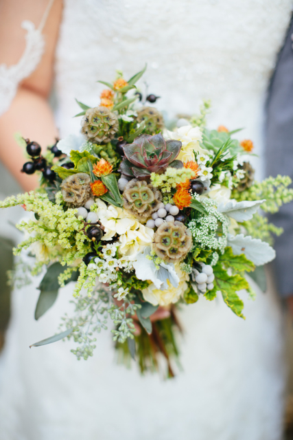 Bridal bouquet by designer Katie Pollard of Color My World Flowers - Nashville, Tennessee, with succulents, scabiosa pods, orange gompherna, wax flower, brunia, scented geranium, cream stock and seeded eucalyptus